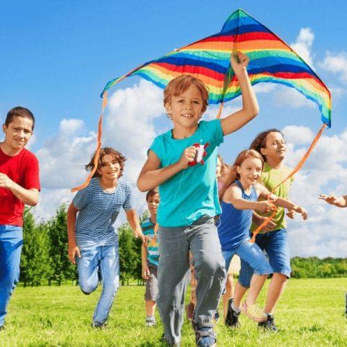 kinderen spelen buiten met vlieger